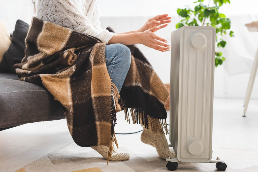 cropped view of girl with blanket warming up with heater in cold room