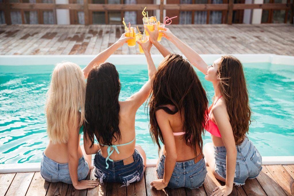 Four cheerful girls having fun at the swimming pool.