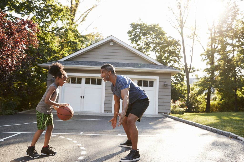 Father And Daughter Playing Basketball On Smooth Driveway Surface At Home